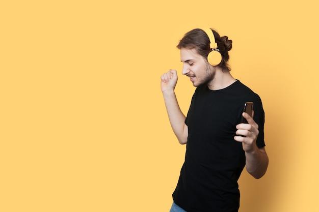 잘 생긴 남자는 여유 공간이있는 노란색 벽에 전화와 헤드폰을 사용하여 음악을 듣고 있습니다.