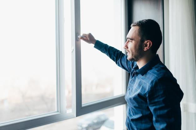 잘 생긴 남자가 집에서 창문을 열어 방을 새로 고칩니다.