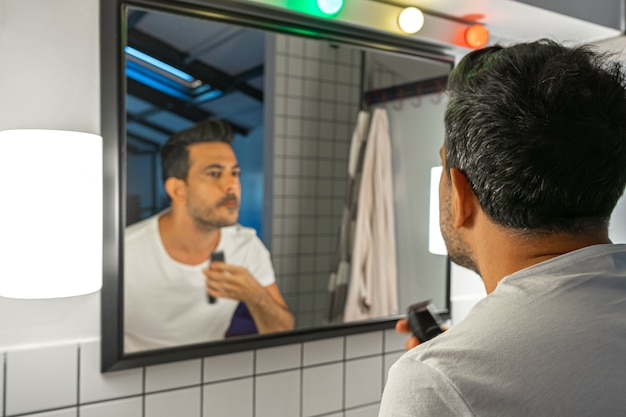 ハンサムな男は、バスルームの鏡の前でトリマーマシンでひげを剃っています。