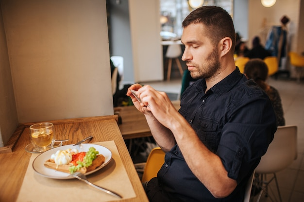 Красивый человек сидит в кафе и фотографирует еду, которую он заказал. он делает это по телефону. парень выглядит очень серьезным и вдумчивым.