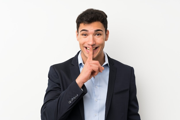 Handsome man over isolated white wall doing silence gesture