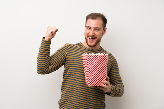 Handsome man over isolated white wall holding a bowl of popcorns