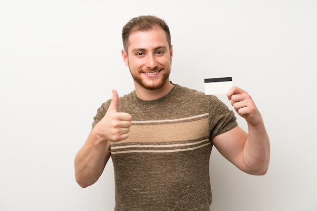 Handsome man over isolated white wall holding a credit card