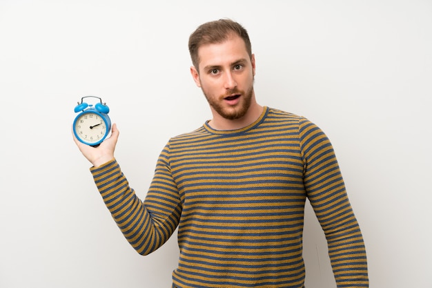 Handsome man over isolated white wall holding vintage alarm clock
