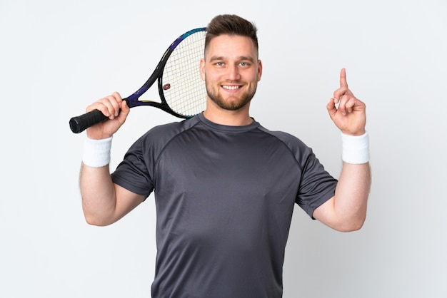 Handsome man isolated on white wall playing tennis and pointing up