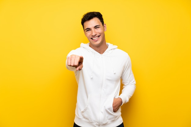 Handsome man over isolated yellow wall pointing to the front