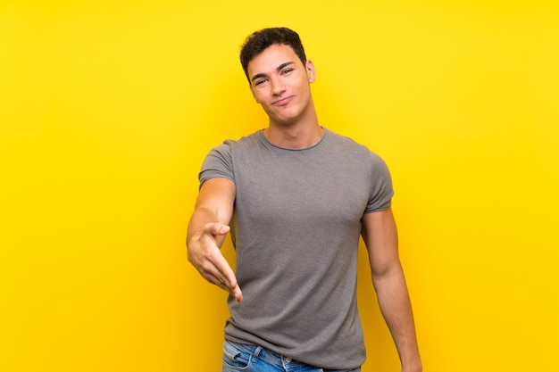 Handsome man over isolated yellow wall shaking hands for closing a good deal