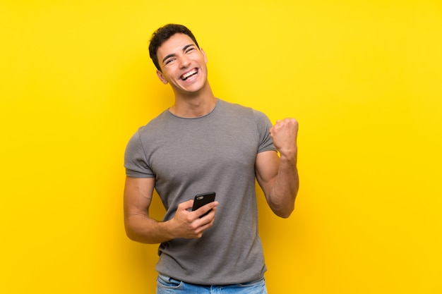 Handsome man over isolated yellow wall with phone in victory position