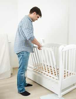 Handsome man in jeans and shirt assembling baby's cot