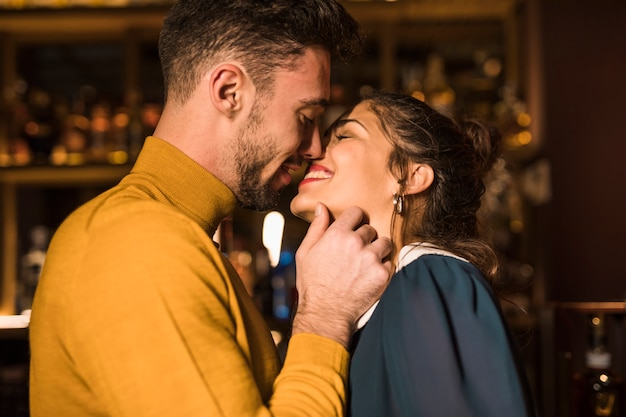 Handsome man kissing cheerful woman