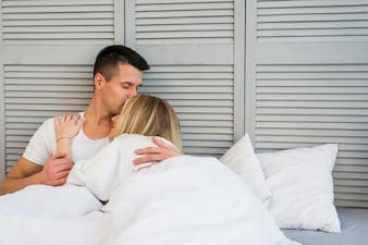 Handsome man kissing young woman lying on bed