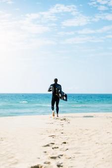 해변에서 실행하는 잘 생긴 남자 kitesurfer.