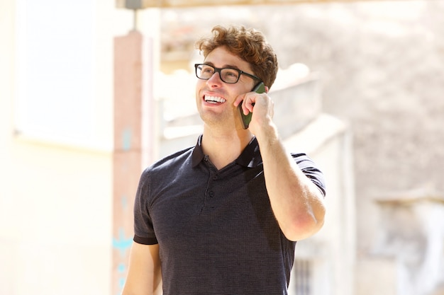 Handsome man laughing and talking on mobile phone