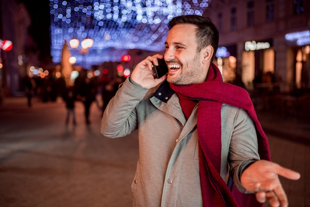 Handsome man laughing while talking on mobile phone at night in decorated city street.