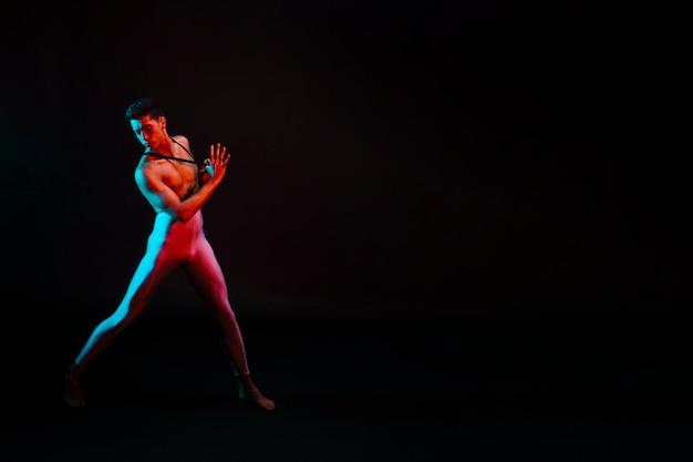 Handsome man in leotard with naked torso dancing in spotlight