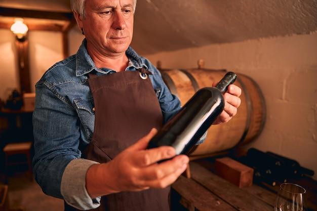 와인 저장고에 서있는 동안 심각한 표정으로 알코올 음료 한 병을보고 잘 생긴 남자