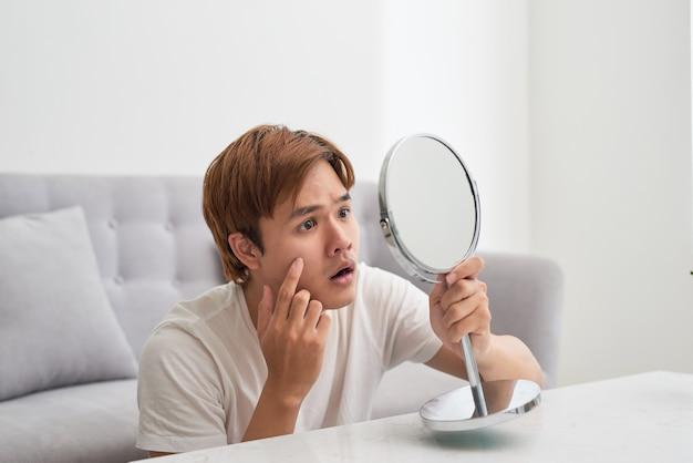 Красивый мужчина смотрит на себя в зеркало. сдавливающий прыщик.