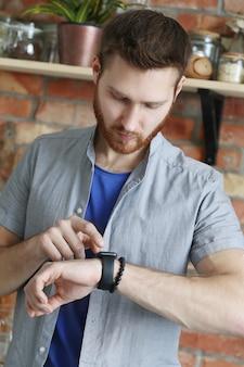 Uomo bello che esamina il suo orologio da polso