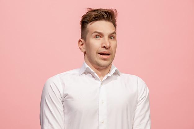 Handsome man looking surprised isolated on pink