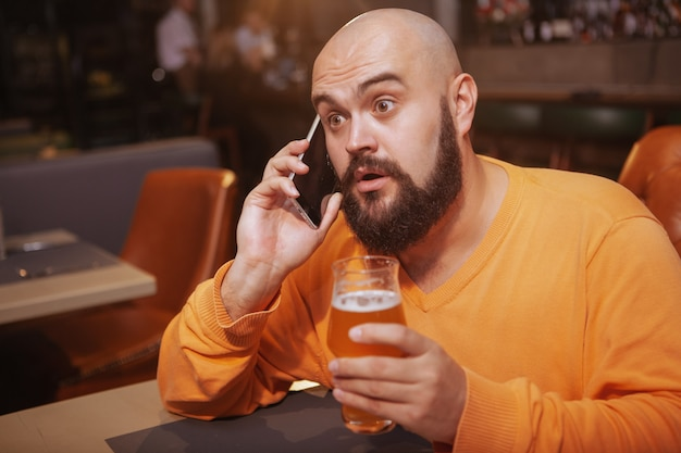 Handsome man looking surprised, talking on the phone while drinking beer at the restaurant
