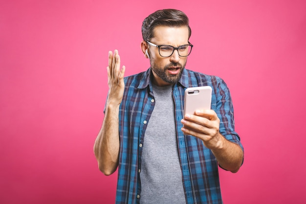 Handsome man looks shocked in smartphone. people, emotions and technology concept.