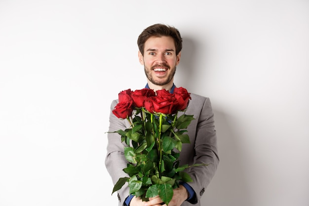 Handsome man in love wishing happy valentines day, giving bouquet of flowers on romantic date, smiling at camera, wearing suit over white background.