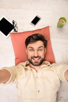 枕の上で床に横たわって自分撮りを作るハンサムな男