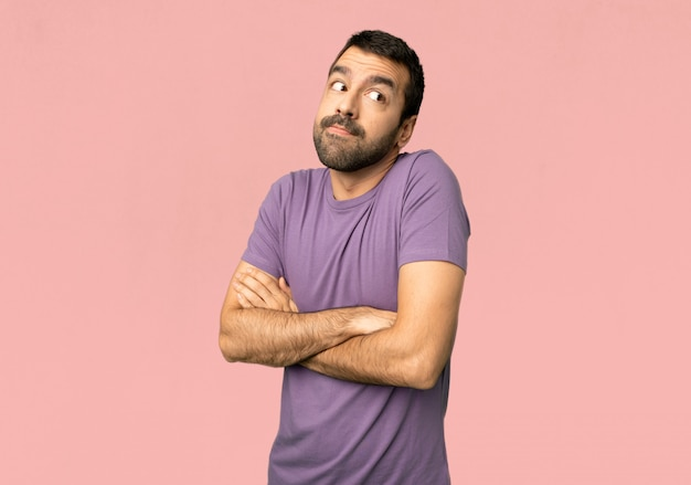 Handsome man making doubts gesture while lifting the shoulders on isolated pink background