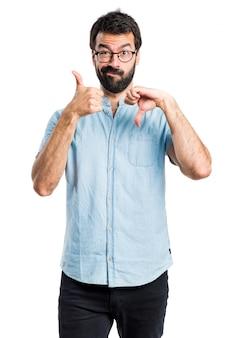 Handsome man making good-bad sign