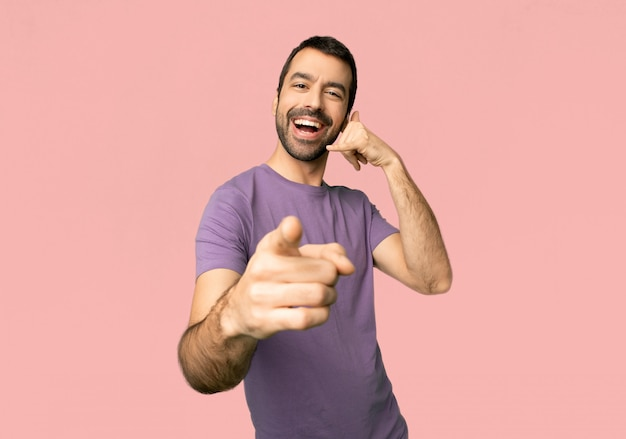 Handsome man making phone gesture and pointing front on isolated pink background