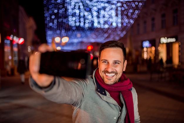 Handsome man making selfie in decorated city street.