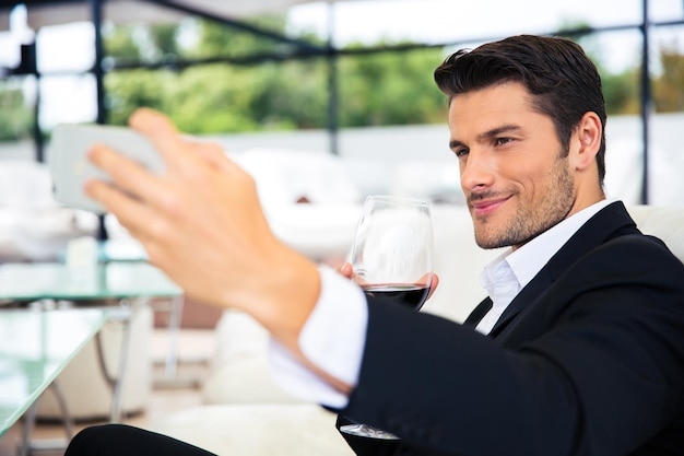 Handsome man making selfie photo on smartphone in restaurant