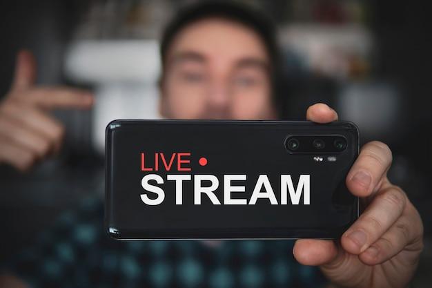 Красивый мужчина делает видеоблог. сосредоточьтесь на смартфоне. молодой видеоблогер снимает контент для своего видеоблога в социальной сети. прямая трансляция через интернет. концепция