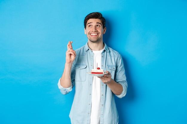 Bell'uomo che esprime un desiderio, festeggia il compleanno, tiene in mano la torta di b-day e incrocia le dita, in piedi su sfondo blu