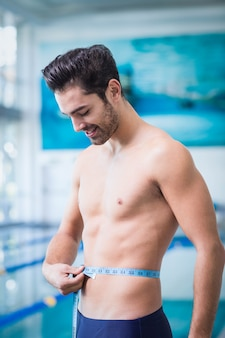 Handsome man measuring waist in the swimming pool