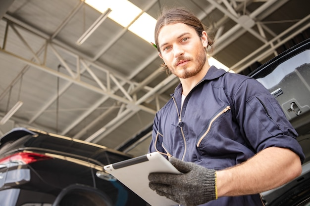 Handsome man mechanics in uniform is working in auto service with lifted vehicle and tablet.