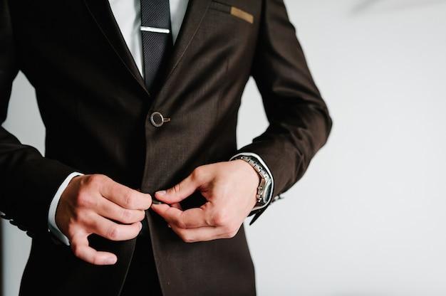 ハンサムな男のモデルは、白い背景、クローズアップのフォーマルなスーツでボタンを閉じます。