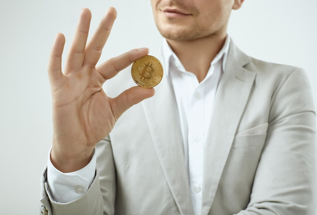 Handsome man model in a fashion gray suit holds a bitcoin