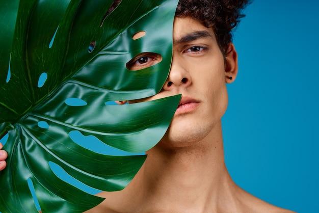 Красивый мужчина голые плечи зеленый лист прозрачная кожа синий фон