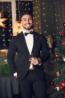 クリスマスツリーの近くのハンサムな男。黒のスーツを着たゲンテルマン。