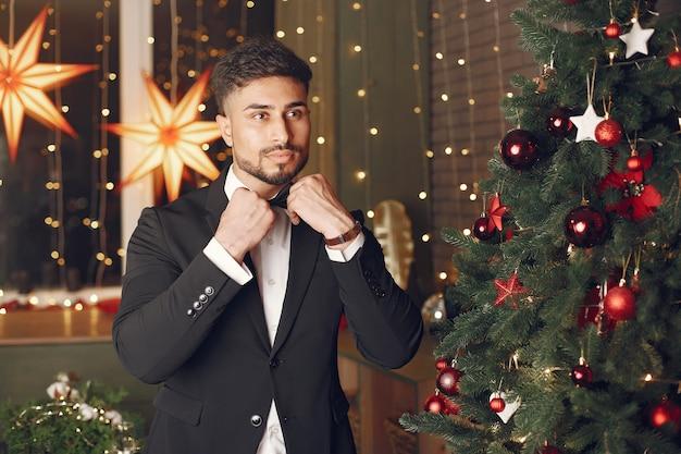 Красивый мужчина возле елки. джентельман в черном костюме.