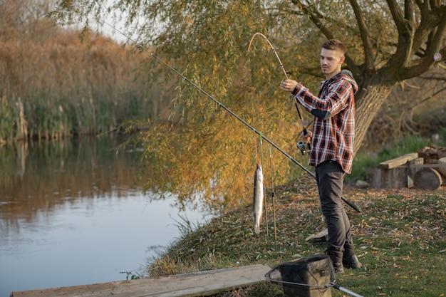 釣りの朝に川の近くのハンサムな男