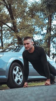 Красивый мужчина возле машины. спортсмен отжался рядом с машиной. автомобиль vs человек