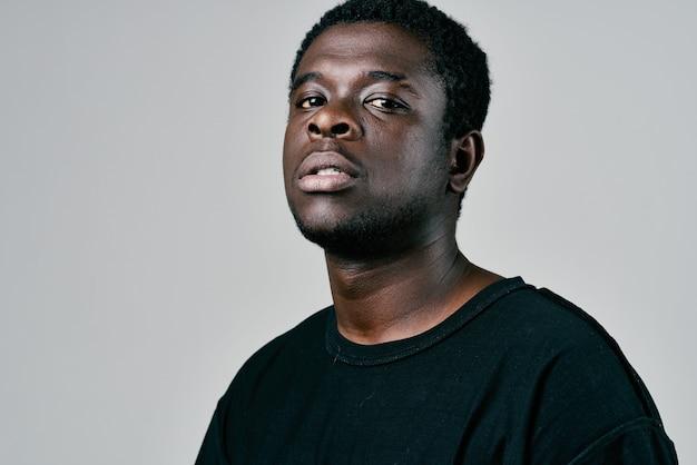 Красивый мужчина африканской внешности в черной футболке с задумчивым взглядом