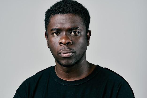 黒のtシャツの物思いにふける表情でアフリカの外観のハンサムな男