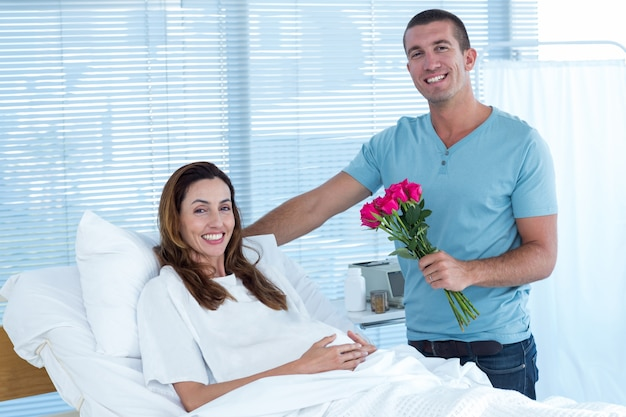 Handsome man offering bouquet of flowers to his pregnant wife