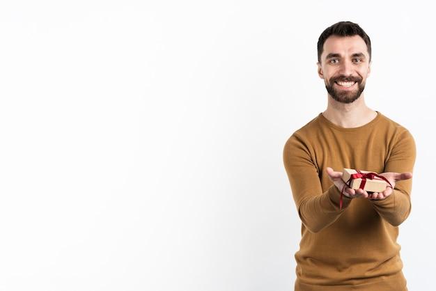 Handsome man offering gift