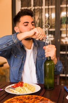Handsome man opening alcohol bottle with opener