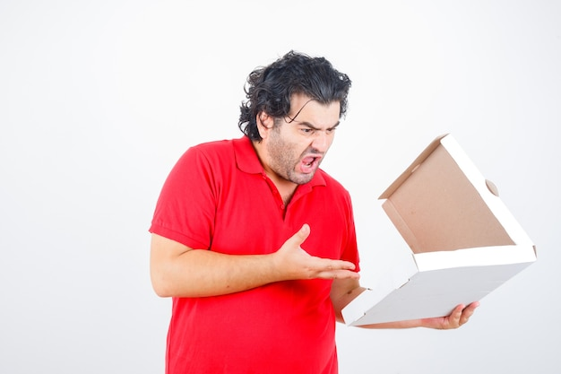 Handsome man opening paper box, stretching hand toward it with angry manner in red t-shirt and looking angry , front view.