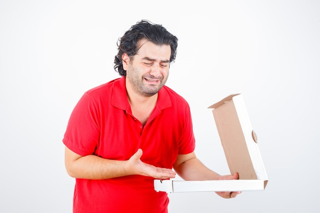 Handsome man opening paper box, stretching hand toward it with disappointed manner in red t-shirt and looking disappointed , front view.